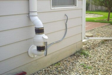 A radon mitigation system in line fan on the side of a house in Nicholasville KY